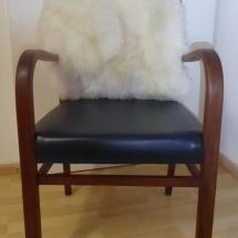 blauer Lederstuhl mit Holzarmlehnen und Fell